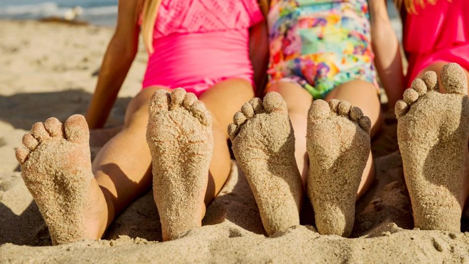 Kids sandy feet at the beach