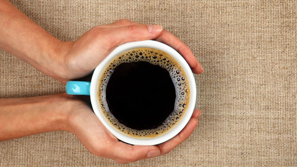 Hands holding a cup of black coffee