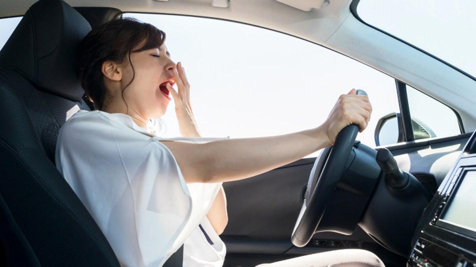 Woman yawning in her car