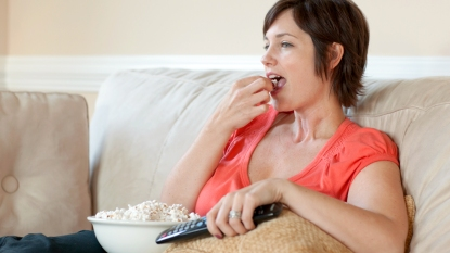 Woman eating popcorn on couch with remote control
