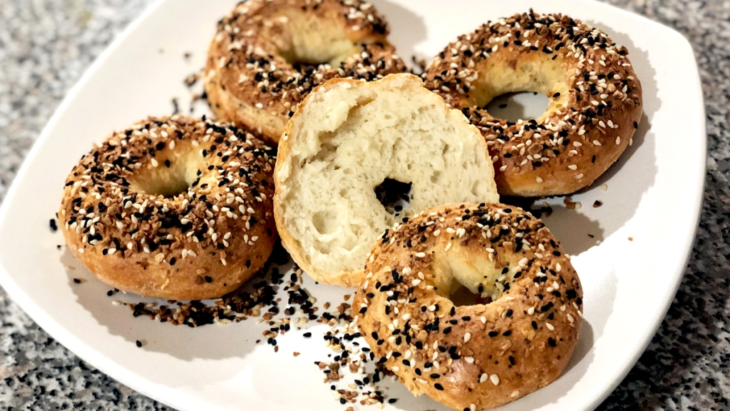 Four everything bagels on a plate