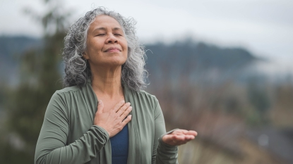 woman breathing deeply outdoors to combat fatigue