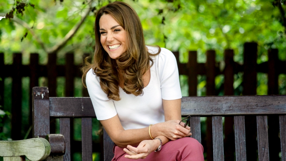 Kate Middleton sitting on a bench smiling