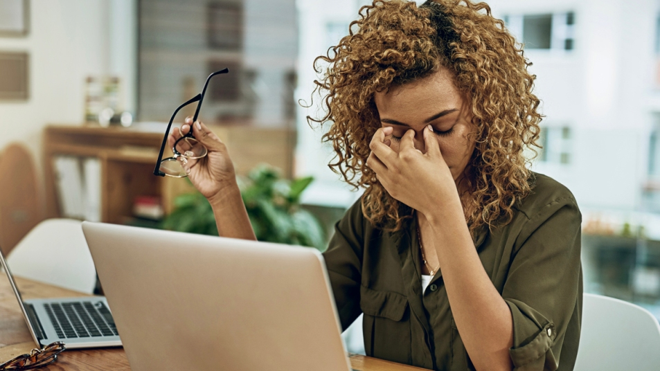 Woman rubbing her eyes with a laptop in front of her