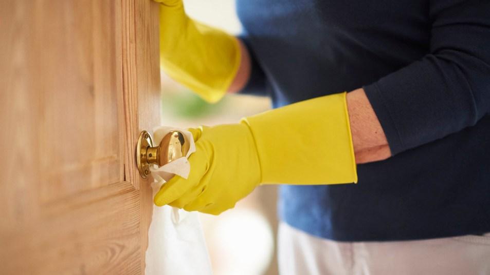 woman wiping down a doorknob