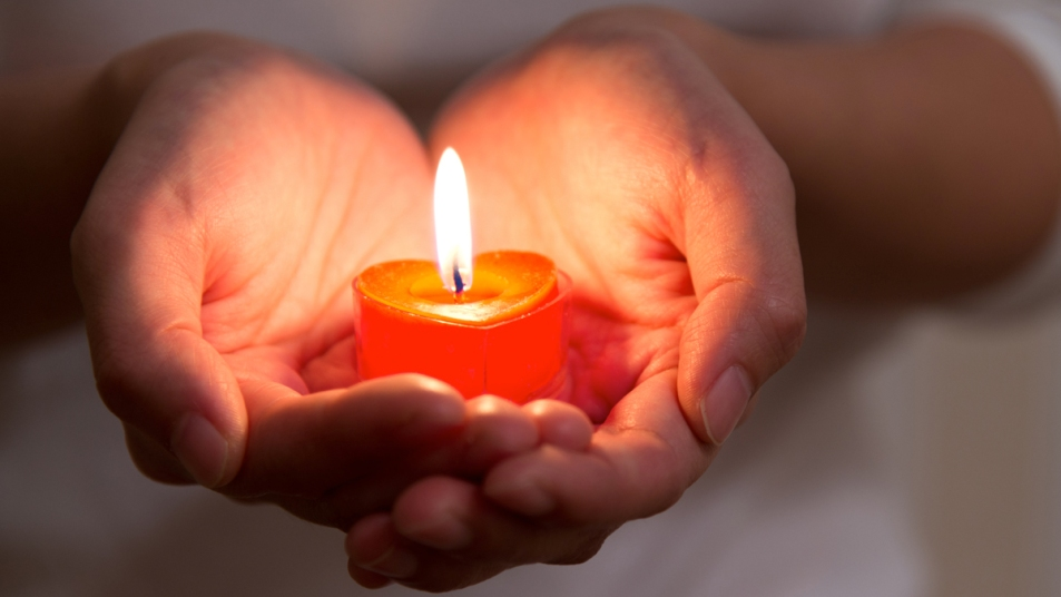 Hands holding heart-shaped candle