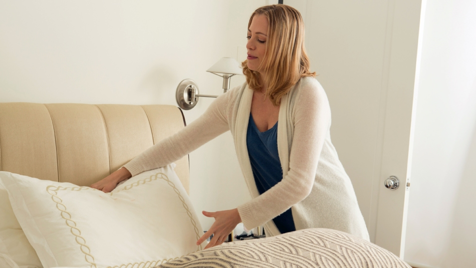 Woman grabbing pillow from her bed