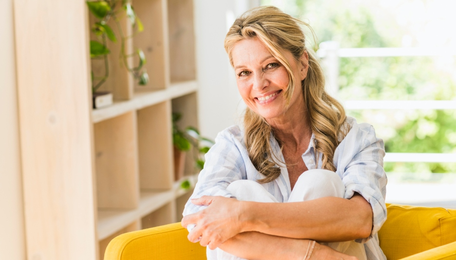 Portrait of smiling mature woman relaxing in armchair at home