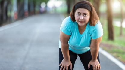 woman exercising outdoors and taking a break