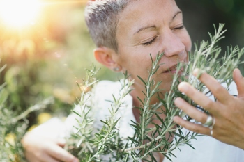 woman smelling rosemary herbs
