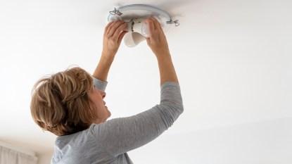 Woman installing a lightbulb