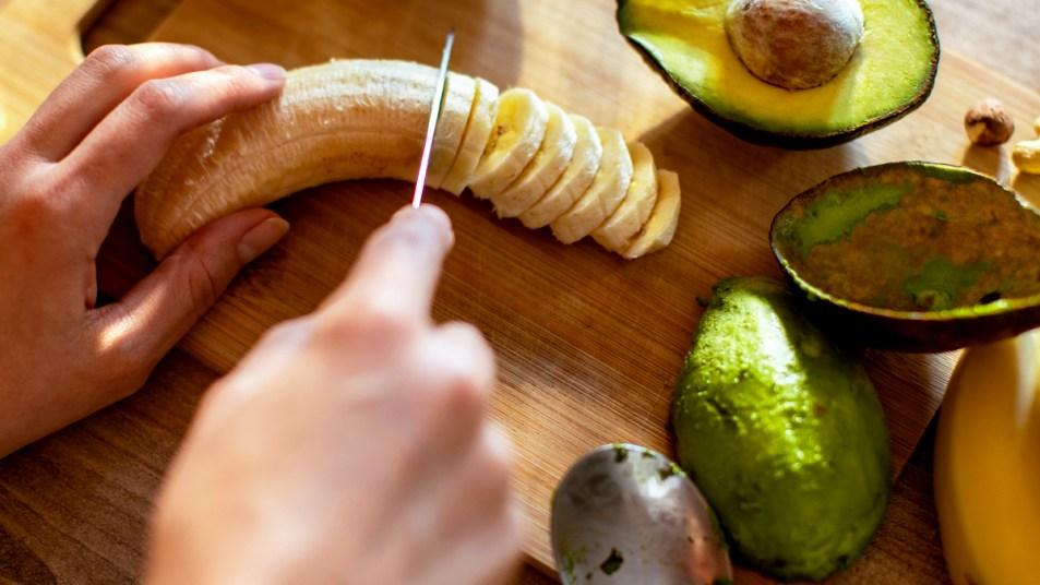 Woman's hand slicing bananas