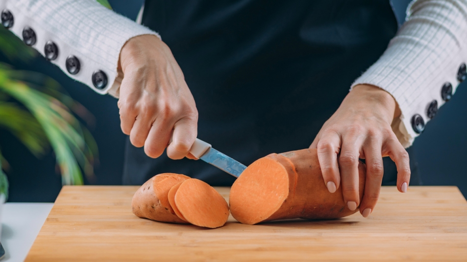 Woman's hands slicing sweet potato