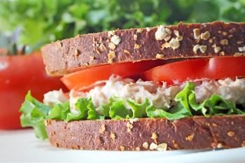 Tuna fish sandwich on whole grain wheat bread with lettuce and tomato.