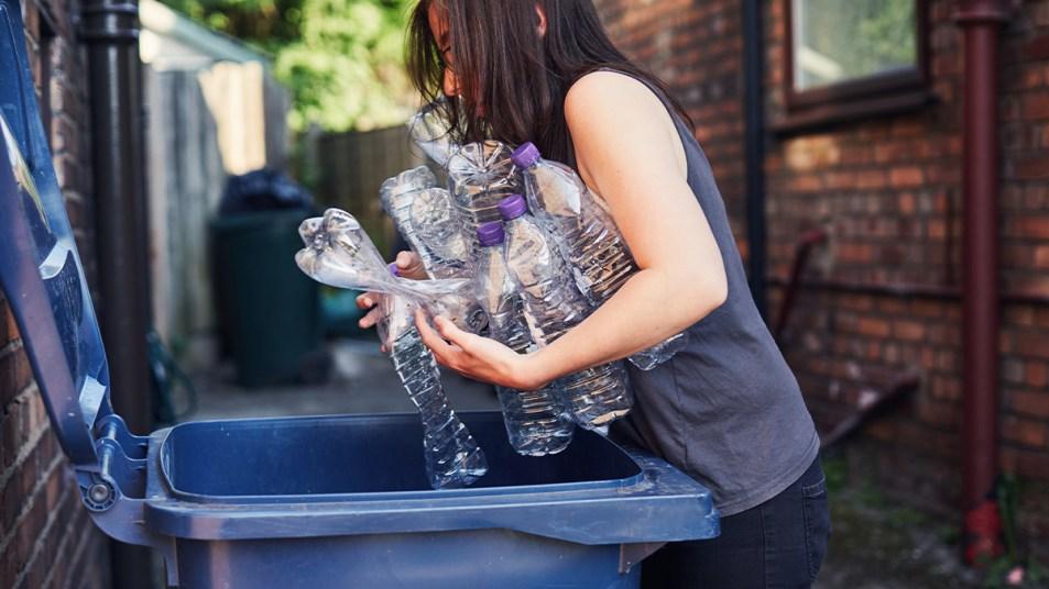 Woman Putting Plastic Bottles Into A Bin