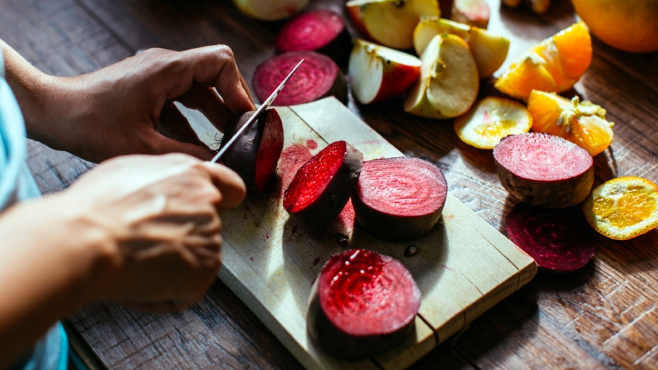 Hands slicing beets with a knife