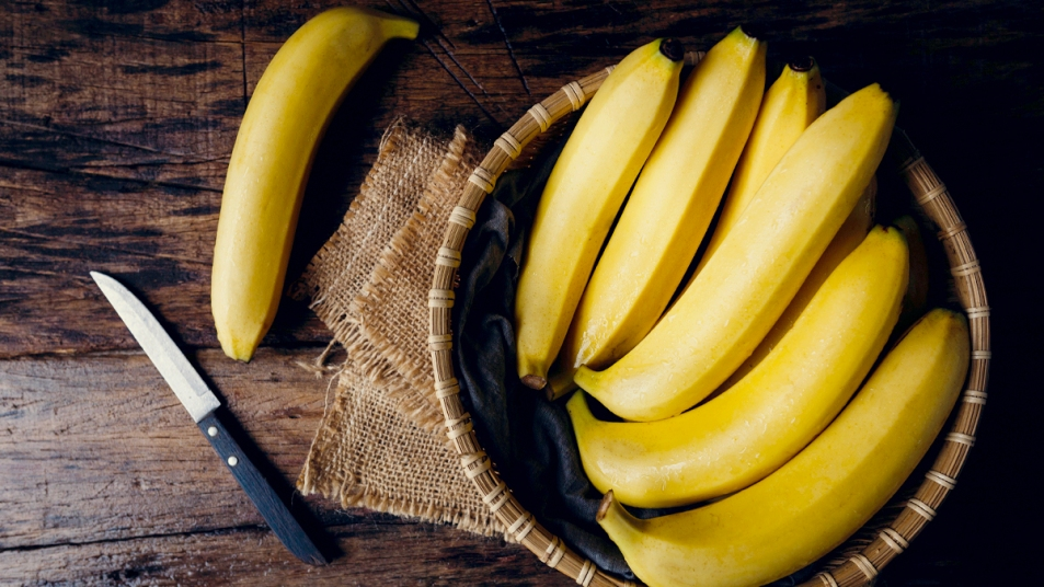 Bananas in a basket with knife next to them