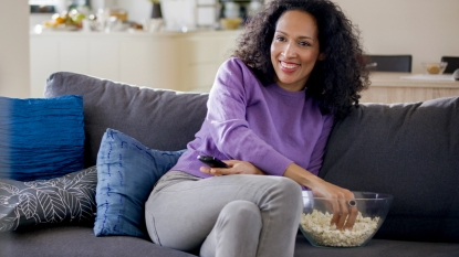 Woman reaching for popcorn on the couch