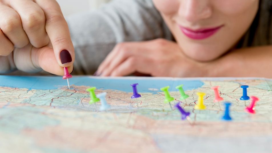 Woman putting colorful pins in a map