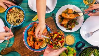 Hands reaching for Mediterranean food