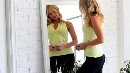 Woman measuring her belly and looking in a mirror