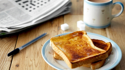 Plate of toast next to coffee and newspaper