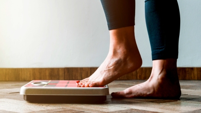 Woman's feet stepping on a scale