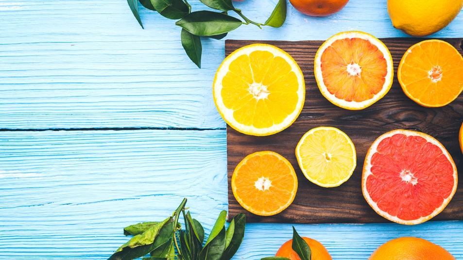 Top view of sliced citrus fruits on blue wooden background