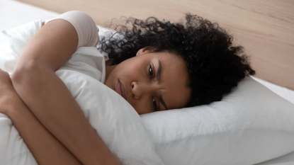 Stressed woman clinging to comforter in bed