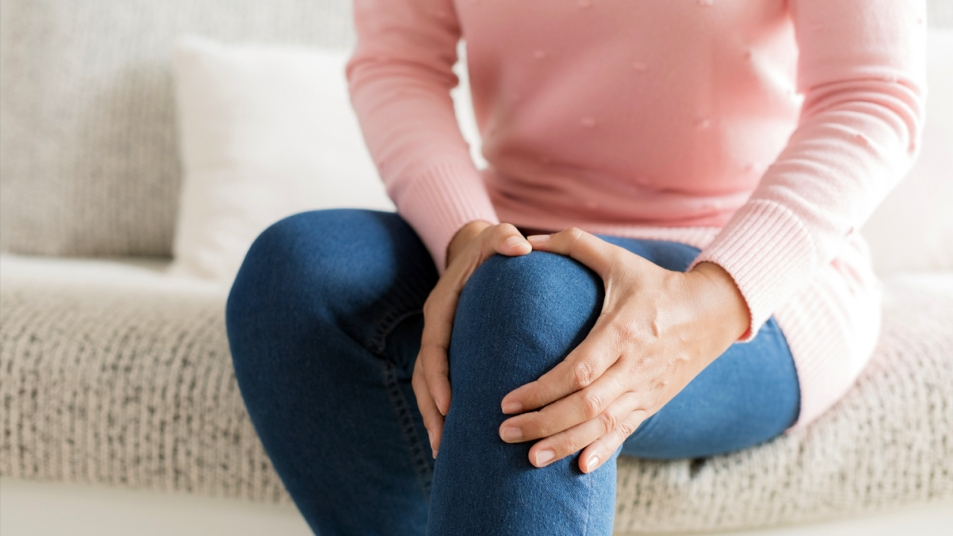 Bottom half of woman holding her knee in pain