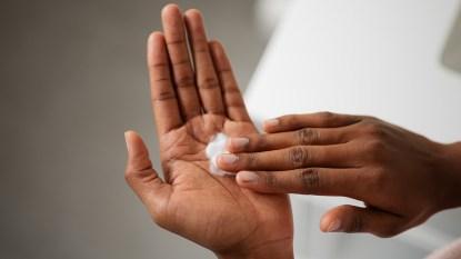 Woman Rubbing Cream Into Her Hands