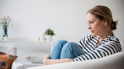 woman feeling stress, sitting in chair holding legs