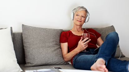 woman listening to music and drinking wine